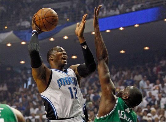 Orlando Magic center Dwight Howard went up to shoot under pressure from Celtics center Kendrick Perkins in the first quarter.