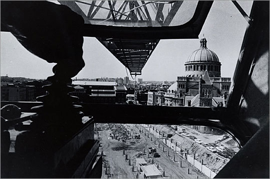 This view from a 100-foot crane shows the construction at the headquarters of the First Church of Christ, Scientist in 1969. In addition to the plaza and reflecting pool, the project also added a church center, administration building, Sunday School building, expanded radio-television facilities, an underground garage, and a public exhibition hall.