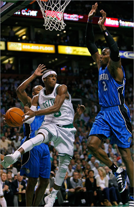 The Celtics' Rajon Rondo dished off as the Magic's Dwight Howard closed in on him in the first quarter.
