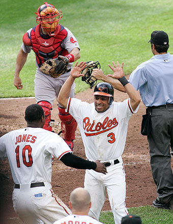 Cesar Izturis (arms raised) and Adam Jones had a lot to celebrate: Izturis scored the winning run and the Orioles' 10-game losing streak ended.