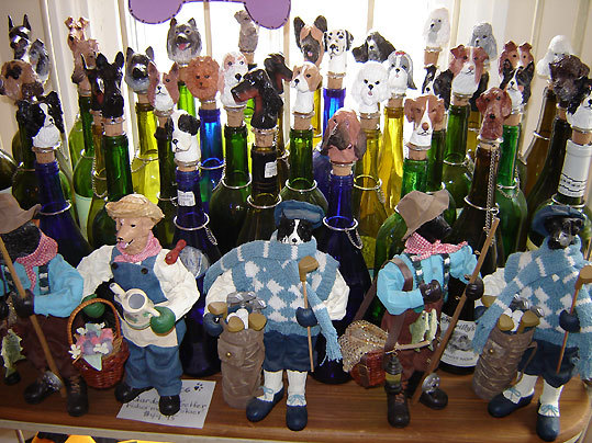 A table of canine-themed wine stoppers and figurines of dogs dressed as golfers, gardeners, and fishermen at Good Dog Goods in Oak Bluffs.