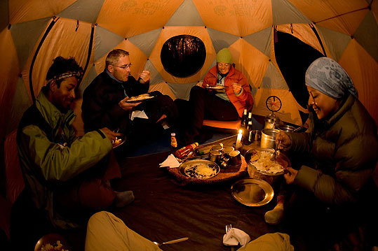 Inside the meal tent on the fourth day of the trek, near Yari in the Karnali River Valley. Clients on this guided trek slept in their own tents, but meals (prepared by the porters) were served inside this shared tent. Jamie McGuinness, who was one of the first people to propose the idea of the Great Himalaya Trail, is second from left.