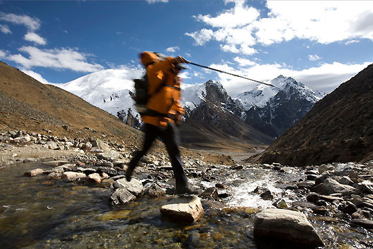 After crossing the highest pass of the trip, the Nyalu Lagna (16,371 feet) Jamie McGuinness jumps through a creek on the way back toward the Karnali Valley on the 13th day of the trek.