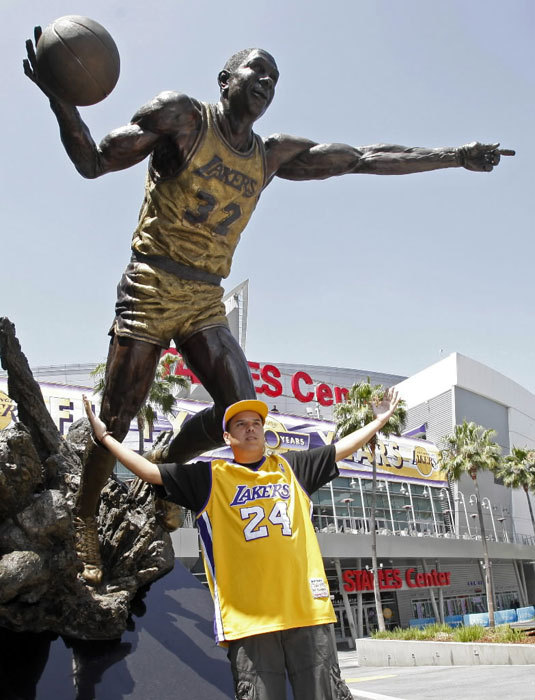 James Gonzalez, 19, of San Bernardino, Calif., poses beneath a commemorative bronze statue of Lakers star Earvin 'Magic' Johnson' as Lakers fans take in the sights at midday outside Staples Center, where the Boston Celtics will battle the Los Angeles Lakers for the NBA championship Thursday, June 17, 2010.