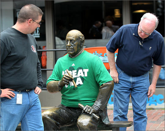 In the Faneuil Hall Marketplace, Paul Riley (right), of Norwood, and co-worker Bob Joy (left), from Pembroke, examined the 'Beat LA' shirt somehow put on a statue of Red Auerbach.