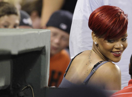 Singer Rihanna looks over her shoulder into the Red Sox dugout as she attended the festive Friday night game at Fenway.