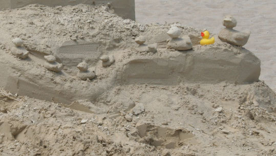 A rubber duck sits amid his sandy family.