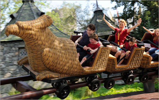 Harry Potter film star Daniel Radcliffe rides the Flight of the Hippogriff attraction with some of the first guests to the new themed area.
