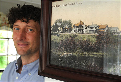 James next to an old photo of the cottages. Bucking the trend toward building big, the Curriers recently renovated and restored their little cottage on Ocean Avenue to its original appearance.