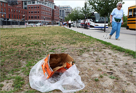 Trash is seen on a dying lawn between North and Hanover streets, and Surface and Blackstone streets.