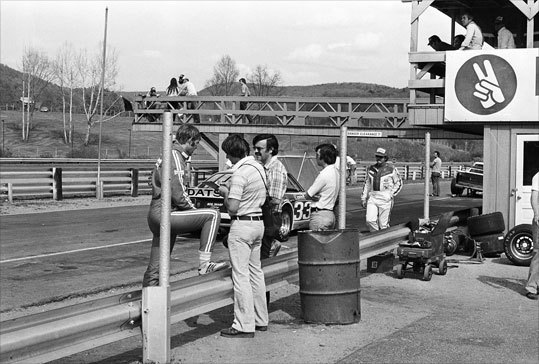 Sam Posey stops to chat in pit lane in 1978.