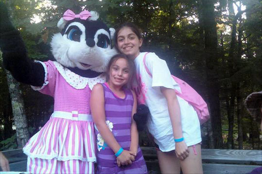 Sisters Olivia and Julia, of Revere, pose with Stinky the Skunk at the Point Sebago Resort in Casco, Maine. Their family went on a hayride, spent time on the beach and enjoyed the gorgeous weather and beautiful lake on their vacation in Maine.