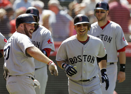 Marco Scutaro (right) celebrates his grand slam with Kevin Youkilis during the eighth inning against the Los Angeles Angels in Anaheim, Calif., on Wednesday. The grand slam broke a 3-3 tie.