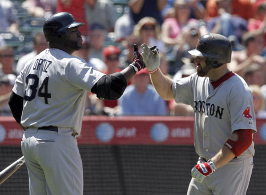 Kevin Youkilis (right) celebrates his home run with teammate David Ortiz against the Angels during the seventh inning to tie the game 3-3 on Wednesday.