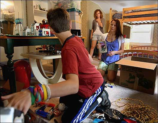 Alexander Gagliardo packs as Teresa Keller and family friend Meagan Franz (in rear) look on.
