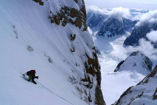 An unknown climber ascends the final stretches of Ham and Eggs with the Ruth Gorge in the background.