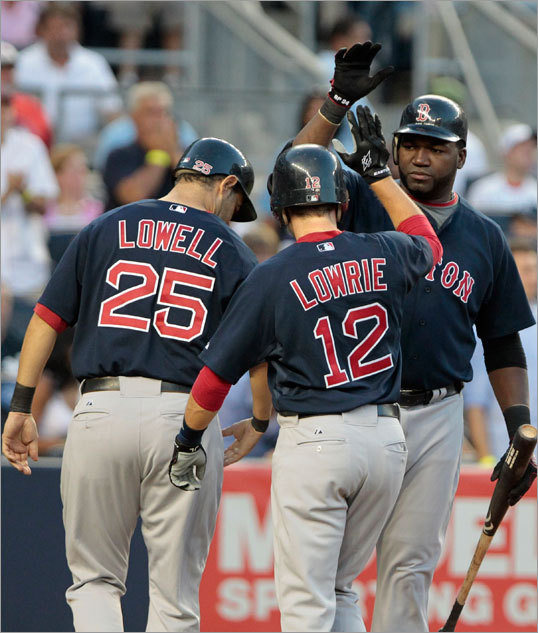 David Ortiz (right) celebrated with teammates Jed Lowrie (12) and Mike Lowell (25) after they scored on a two-run double by Marco Scutaro during the second inning. The Red Sox went on to win 6-3 Friday.
