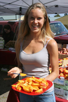 Mickey Davis, who is studying nutrition science and sustainable agriculture in college, hands out samples of Frog Hollow Farm peaches at one of Berkeley's farmer's markets.