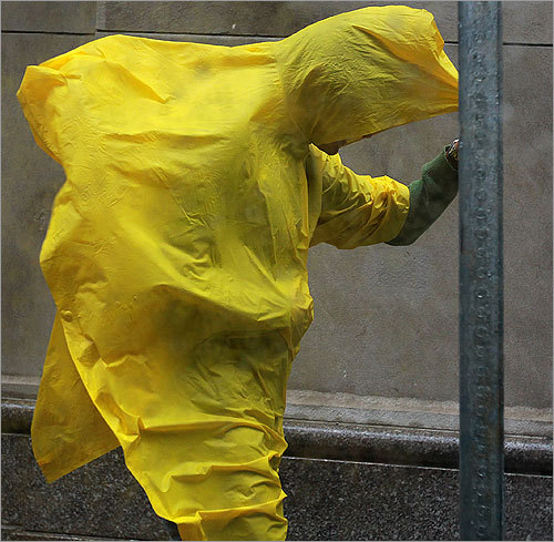 On School Street, fierce winds took their toll on one pedestrian's yellow poncho. Winds gusted higher than 30 miles per hour in parts of Boston.