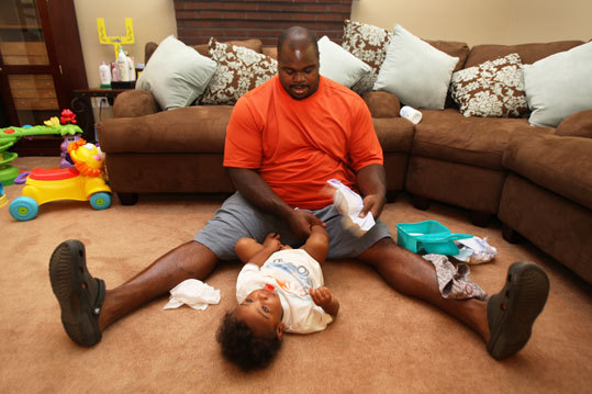 Wilfork uses a special technique when changing the diaper of his son, David Dream-Angel, so the boy can't scramble away from his 6-2, 325-pound dad.