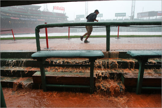 WESTON APPELFELLER, Fenway Park grounds crew manager, runs through a downpour as water pours into the Red Sox dugout, Aug. 4, 2010 -- 'I was just going to canvas alley and grabbing 50-pound bags of Turface; it's an infield conditioner but we stack them up when it floods to build a dam to keep the water from going down into the Red Sox' batting tunnel. It works just like sandbagging. Honestly, at that time there was absolutely nothing going through my head but, 'Man, I hope it quits raining. I don't know what we're going to do if it doesn't quit raining.' I went to Ohio State and studied turf grass science. I work on grass, I don't know a lot about building dams, but that worked pretty good. What happens here is the field drains, and when the city drains get backed up all the water coming off the field and out of the stands has nowhere to go, so it just starts shooting water back up at us. The dugout itself was flooded, but the dam we built held the water out of the tunnel underneath. I could see some players down there. The worst I saw it was during the Futures at Fenway, we didn't get the dam built in time and it did flood the tunnels. It's just an old ballpark and an old city. I was soaked through and through all night.'