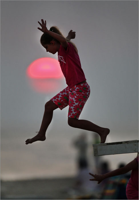 Ellie Martin, 8, of Arlington, Va., at Madaket Beach, Nantucket Island, just before sunset, Aug. 31, 2010 -- 'We got to jump off the lifeguard chair, and it was really fun. I felt like I was flying but I was really just going down. I saw lots of things -- the clouds and the ocean and the sun. It looked pinkish -- just like a glow stick. I think I might be a lifeguard when I grow up. I think that might be fun. I like really tall heights. You get the really tall chair. But the ocean is really salty. The water gets in my mouth and I have to spit it out. That's really gross. I start the third grade on Tuesday so this probably was my last jump.'