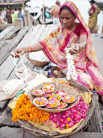 Along the Ganges, a woman arranges flowers as offerings in preparation for the Aarti - a ritual where light and songs are offered to Hindu dieties.