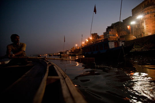 Rowing down the Ganges river in Varanasi beneath the city's ghats and temples.