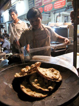In Delhi, a cook pulls cooked naan bread from a tandoori oven.