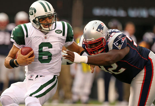 The New York Jets' Mark Sanchez (6) was sacked by the Patriots' Gerard Warren Sunday at the New Meadowlands Stadium in East Rutherford, New Jersey.