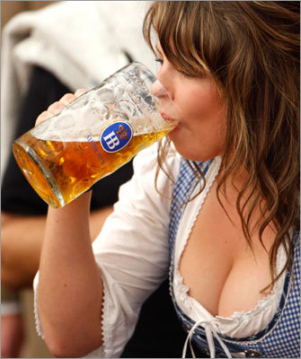A woman dips into a mug of beer.
