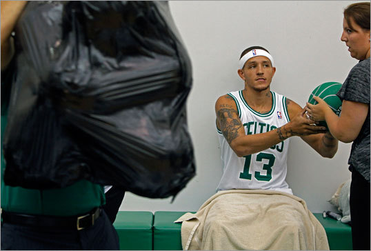 Newly-acquired Celtics guard Delonte West signed a basketball with a bag full of balls looming in the foreground.