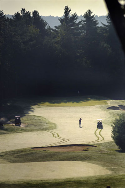 A golfer watches his shot amid early morning dew on the 10th hole.