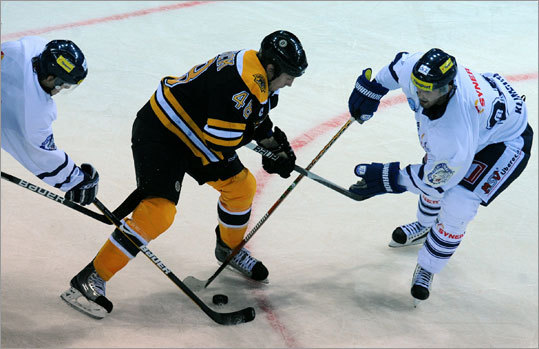 The Bruins' Matt Hunwick battled Liberec's Jan Visek (left) and Tomas Klimenta (right) during a preseason NHL game in Liberec, Czech Republic. It was the second game during the Bruins' tour of Europe, where they will open the NHL regular season in Prague on Saturday against the Phoenix Coyotes.