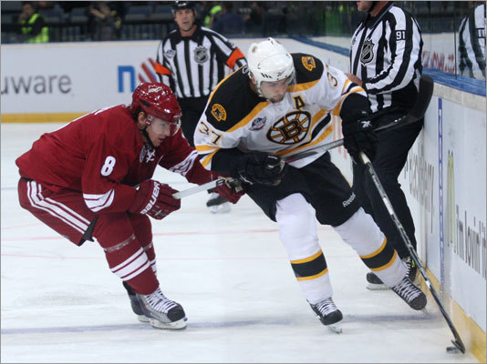 Scottie Upshall (left) of the Phoenix Coyotes challenged Bruins center Patrice Bergeron in the first period of a game played in Prague, Czech Republic.