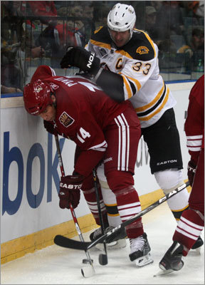 Fresh off signing a contract extension with the team, Bruins defenseman Zdeno Chara (right) did some dirty work along the boards against Phoenix's Taylor Pyatt.
