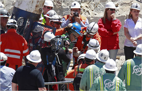 Omar Reygadas, center, wearing a blue helmet, was the 17th miner to emerge from the capsule.