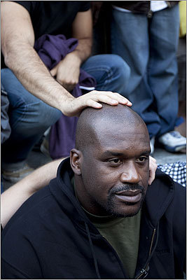 People touched Shaq's head while he posed.