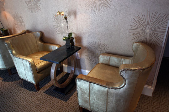 A seating area in the hotel, where creative combinations include crown molding and mirrored nightstands in the rooms and 19th-century French limestone and wallpaper with gold starbursts in the lobby-lounge.