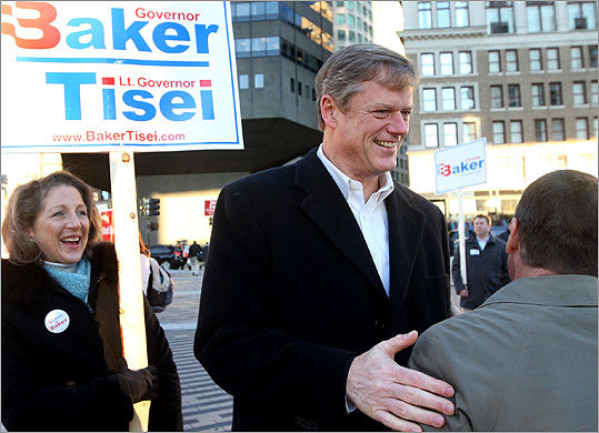 Republican gubernatorial candidate Charles D. Baker greeted people at South Station in Boston this morning as his wife, Lauren, left, held a campaign sign.