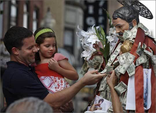 Rafael Pieretti -- with his daughter, Isabella Pieretti, 6 -- pins money on the statue of St. Joseph during the St. Joseph Feast Grand Procession on July 26, 2009.