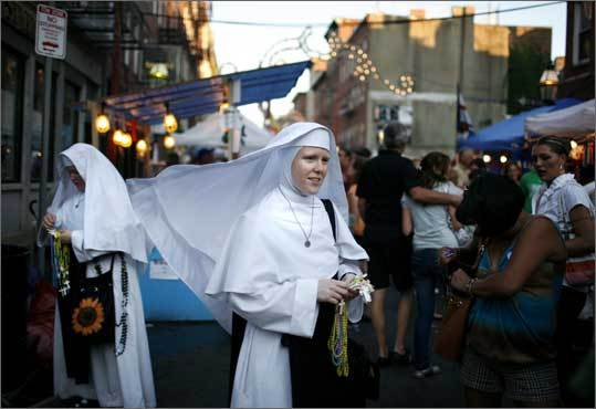 Sister Cecilia, center, and Sister Catherine of Lawrence hand out rosaries on Fleet Street during the 98th annual Fisherman's Feast on Aug. 17, 2008.