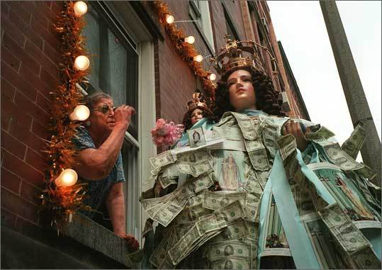 Maria Nastasi gives an offering to the Madonna Delle Grazie during a procession for the Madonna on July 14, 1997.
