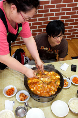 Budae jjigae, or army base stew, was traditionally made from surplus food from US Army bases. Today, you'll still spot chopped up hot dog, canned ham, and the random bean or piece of elbow pasta. Here, like in many restaurants in Seoul, a woman working at the Ko-Am restaurant helps prepare the dish as it cooks over a stove on the table.