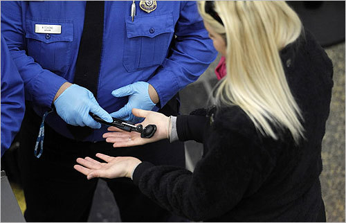 A TSA agent wiped an explosives-detecting device over the hands of a traveler as she underwent security screening at Ronald Reagan Washington National Airport in Washington D.C. on Wednesday.