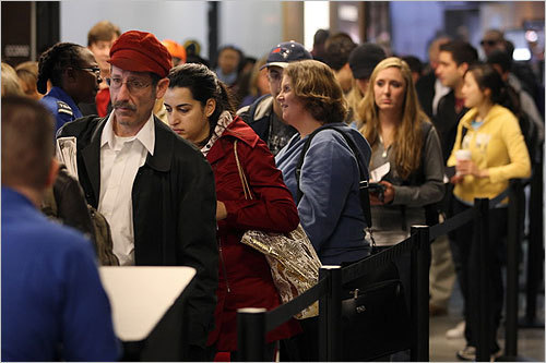 A crowd waited to go through security in Terminal B at Logan International Airport.
