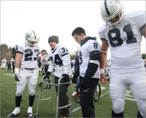 St. John's Prep team manager Jared Coppola (34), who was paralyzed by a football injury in 2009, walked to midfield to participate in the coin toss prior to the St. John's-Xaverian game with his brothers, St. John's running back Tyler Coppola (23) and Brandon Coppola (8), who also was forced to stop playing football because of a fractured vertebra. St. John's, led by Tyler Coppola's two touchdowns, went on to defeat Xaverian and earn a playoff berth. They were joined by senior captain Ryan Delisle (81). Read Bob Holher's story on the Coppola brothers