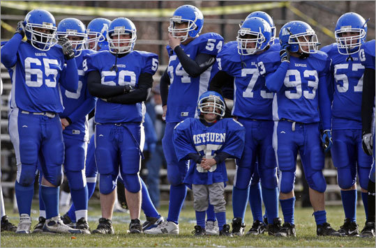 Five-year-old Matthew Feole (85), whose brother Derek (not pictured) is a senior defensive lineman on the Methuen team, joined the big boys on the field during pregame warmups before Methuen hosted Dracut on Thanksgiving morning.