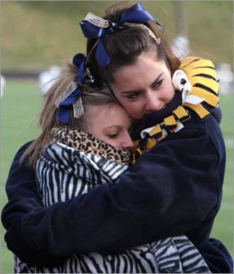 Pope John cheerleaders Tatiana Balistreri (left) and Julie Samopoulos huddle to keep warm while waiting for the start of the football game against Lowell Catholic at Chelsea High School.