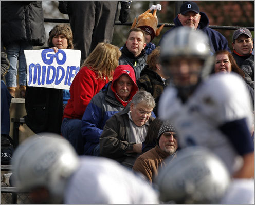 A Dracut fan held a sign for her 'Middies' as their offense came to the line of scrimmage for a first-quarter play.